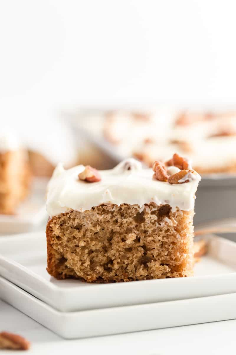 Slice of spice cake on two plates with cream cheese frosting and pecans