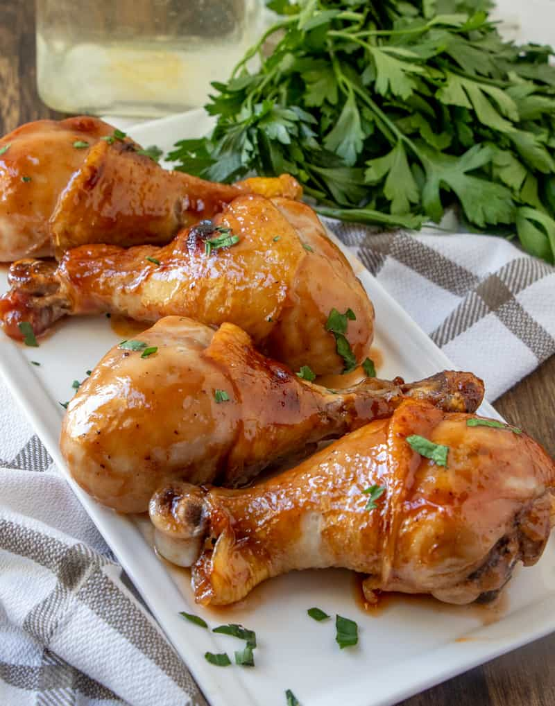Four baked chicken drumsticks on platter with parsley in background
