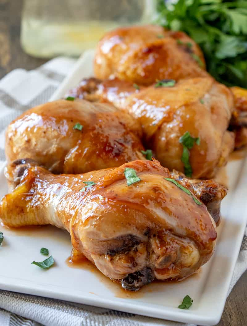 Chicken Drumsticks on platter glazed and sprinkled with chopped parsley