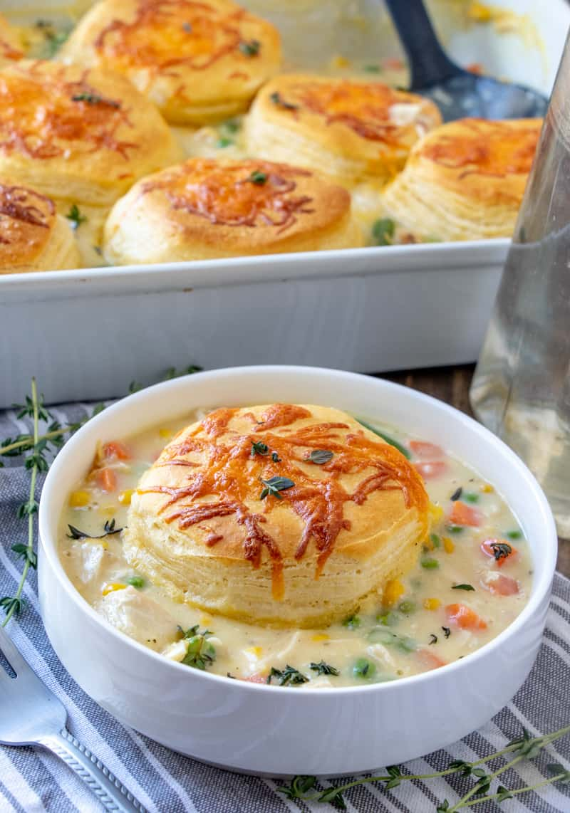 Casserole dish in background and bowl of the chicken pot pie casserole recipe in front with fork and thyme sprigs