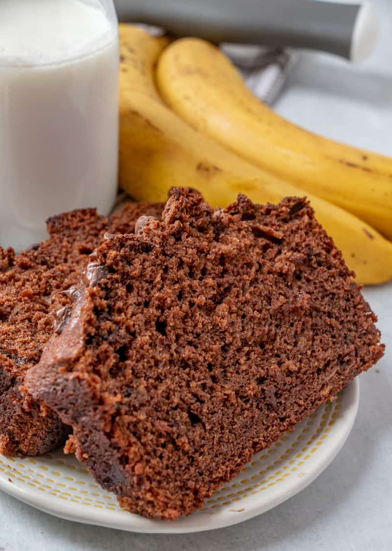 Two slices of chocolate banana bread on plate with bananas in background