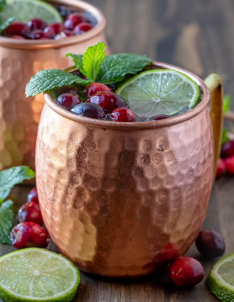 Close up photo of copper mugs showing Moscow mules with cranberries mint and limes
