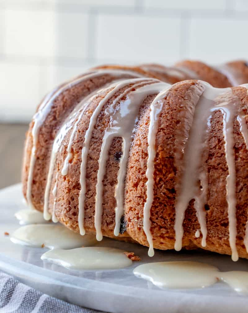 Bundt cake on serving tray with glaze dripping over top