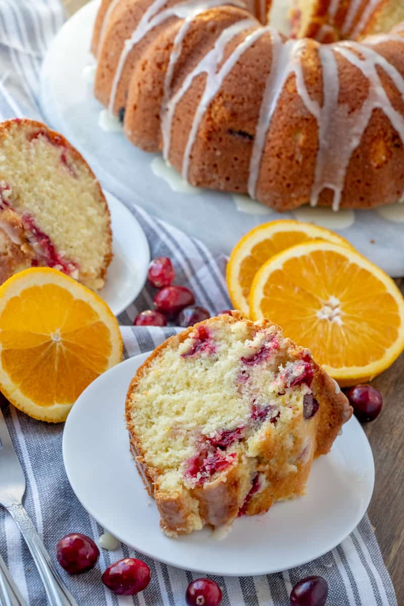 Bundt cake on serving tray with two slices on white plates and slices of oranges and cranberries