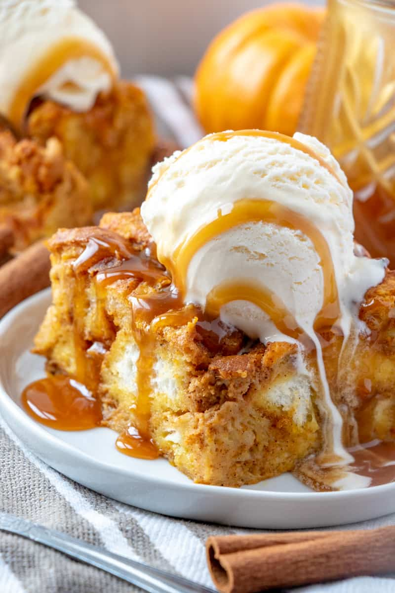 Slice of Pumpkin Bread Pudding on plate with scoop of ice cream and caramel sauce drizzling down