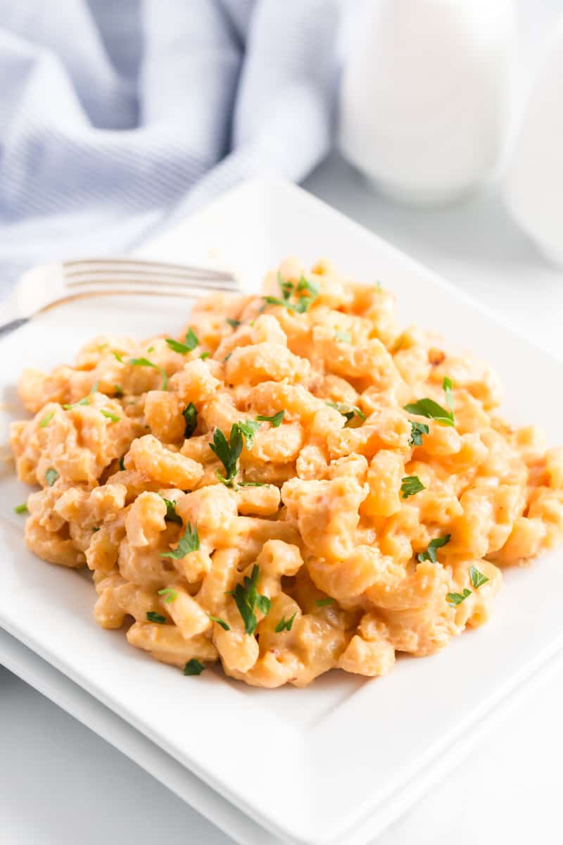 Slow Cooker Mac and Cheese on white plate with parsley