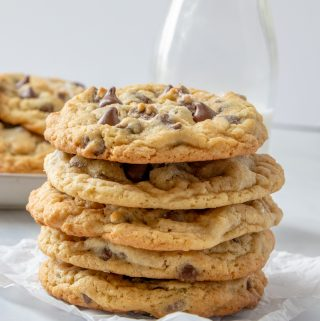 Flour cookies stacked on top of one another in front of milk glass