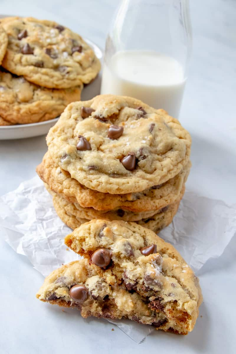 Stacked cookies with a cookie broken in half showing inside and gooey chocolate
