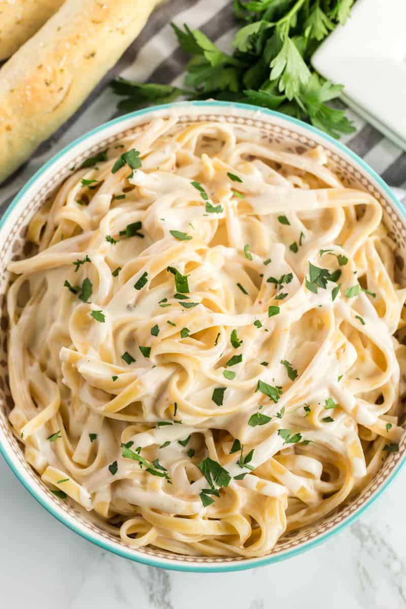 Homemade Alfredo Sauce overhead shot poured over pasta with breadsticks an parsley