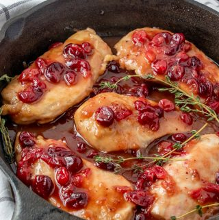 Chicken in skillet soaking in sauce garnished with herbs