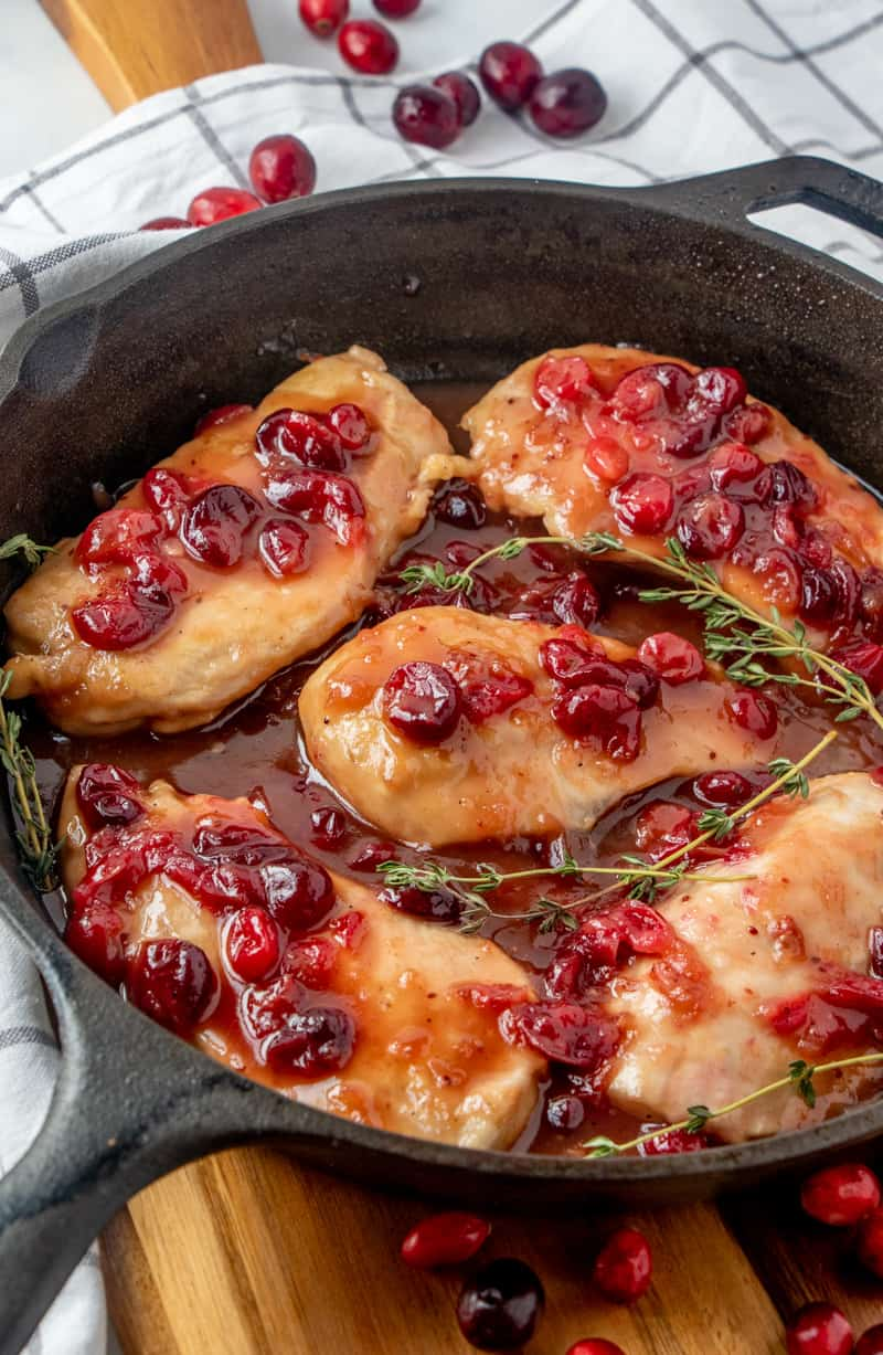Cranberry Chicken in cast iron skillet with sprigs of thyme garnishing dish