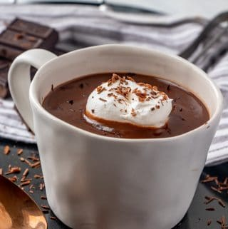 Side view of hot chocolate in mug with whipped cream and chocolate shavings