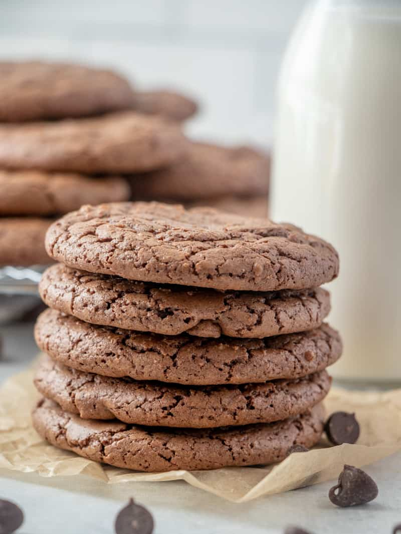 Close up of brownie cookies stacked up on top of one another with chocolate chips surrounding them
