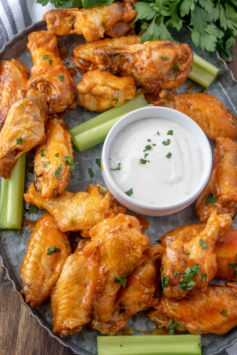 Overhead photo of buffalo wings on tray with celery and ranch with parsley