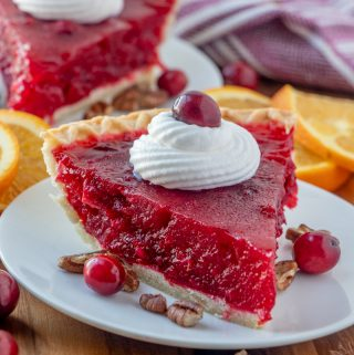Cranberry pie on white plate topped with whipped cream and a cranberry