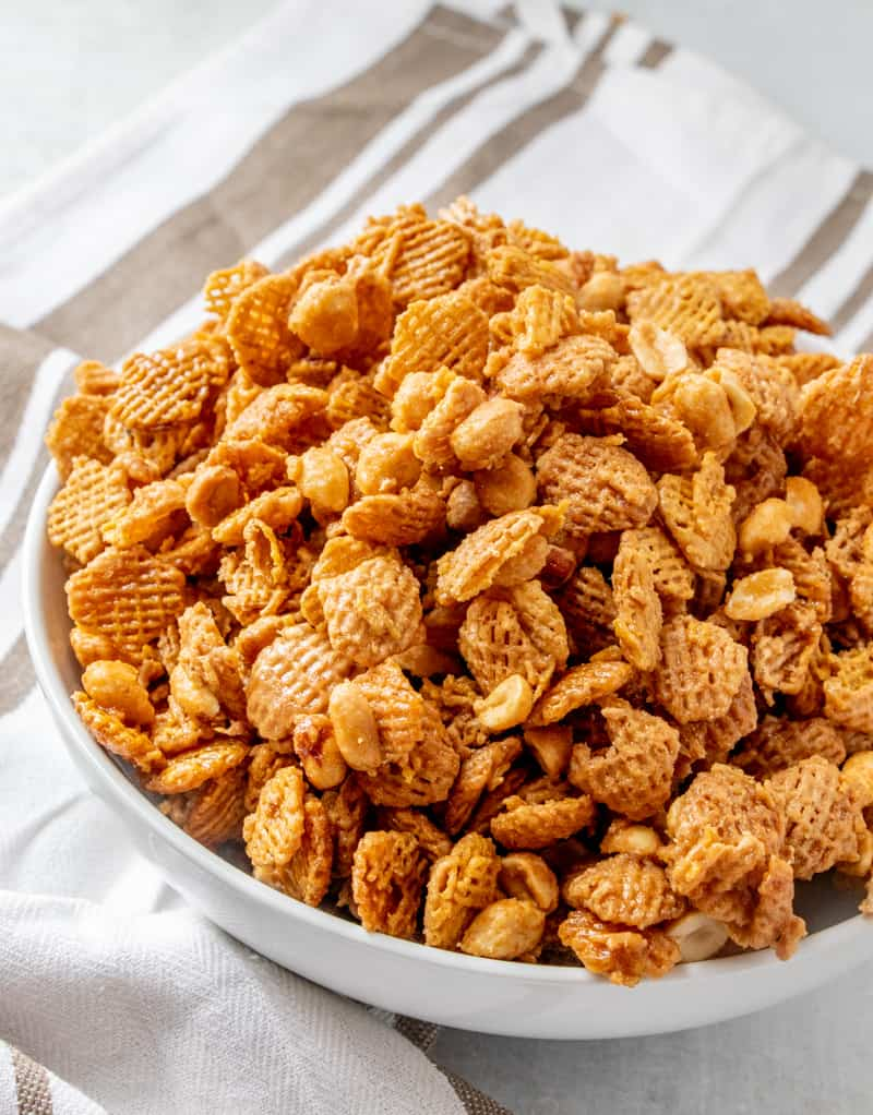 Bowl full of crispix mix recipe showing coated cereal and peanuts