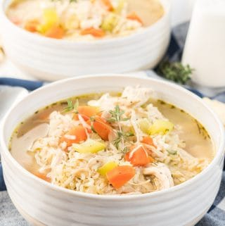 Two soup bowls filled with soup topped with vegetables and thyme sprigs