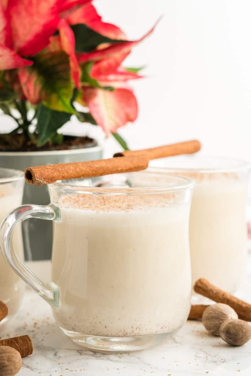 Side view of creamy eggnog in glasses with cinnamon stick on top