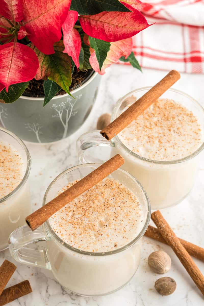 Three glasses of eggnog in mugs with cinnamon sticks over the top of glasses