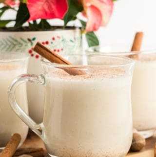 Clear glass of homemade eggnog with cinnamon stick garnish