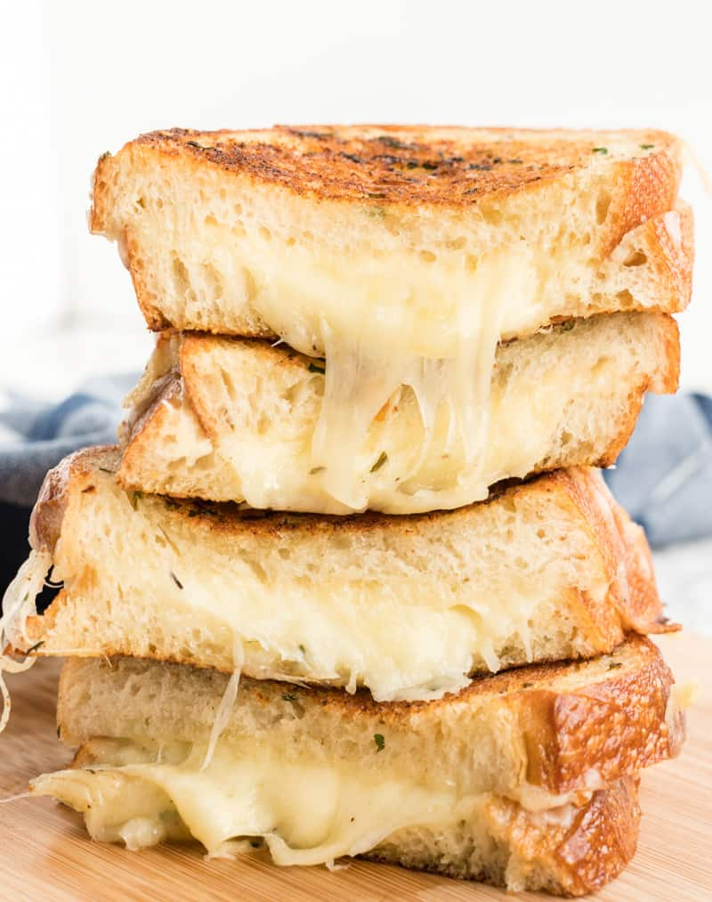 Grilled Cheese Sandwich stacked on top of one another with melty cheese hanging out