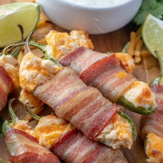 Close up photo of stacked jalapeno poppers showing melty cheese and cooked bacon