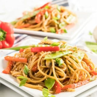 Lo mein plated showing vegetables and topped with sesame seeds