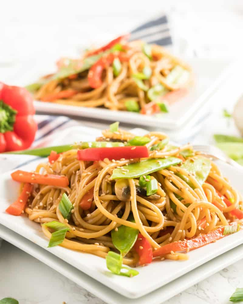 Vegetable Lo Mein on white square plate topped with sesame seeds and sliced green onions