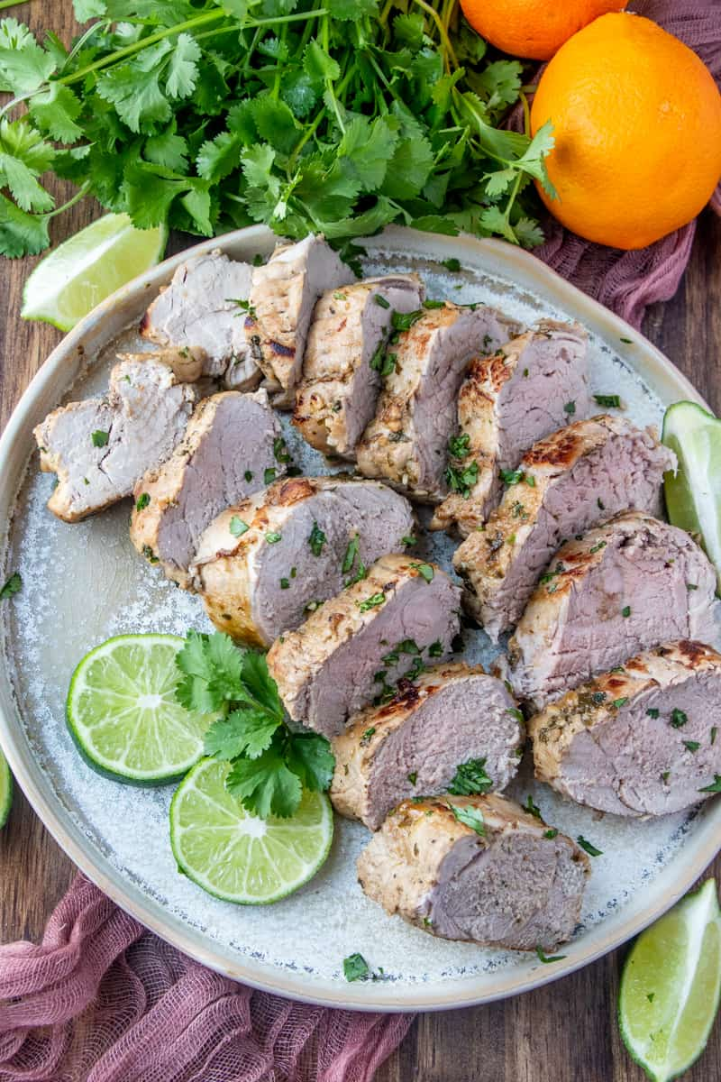 Overhead photo of sliced pork on plate garnished with limes and cilantro