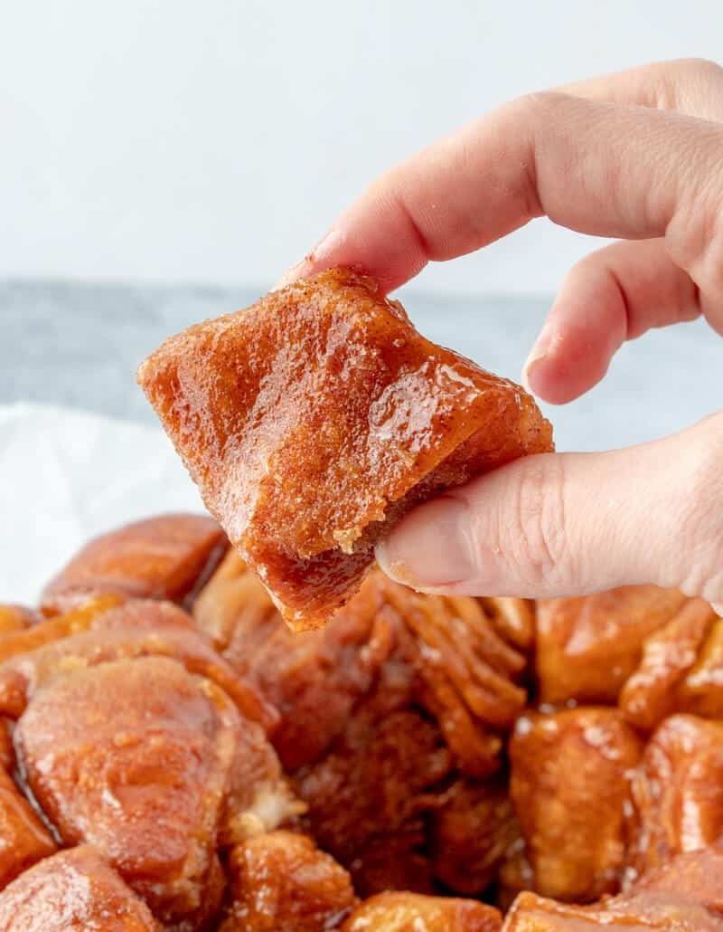 Hand holding a piece of biscuit from monkey bread showing the caramel, cinnamon and sugar