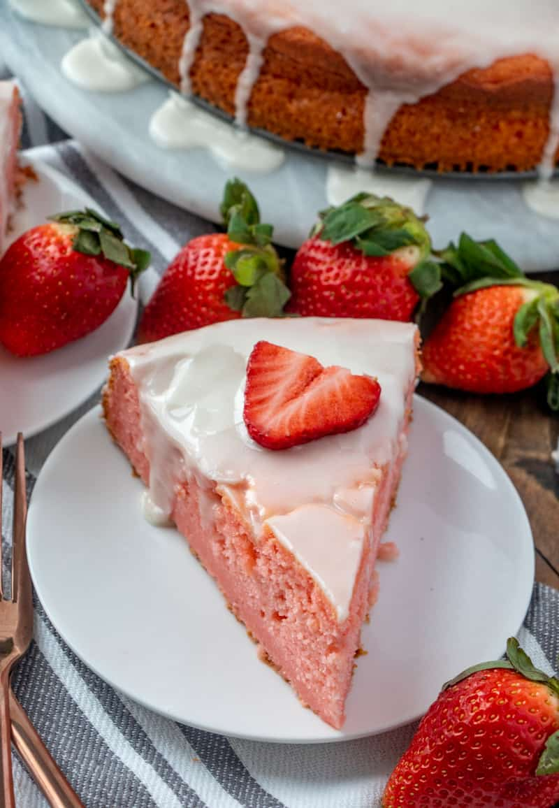Overhead photo of slice of cake on white plate surrounded by strawberries