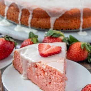 glazed ricotta cake on plate topped with a slice of strawberry