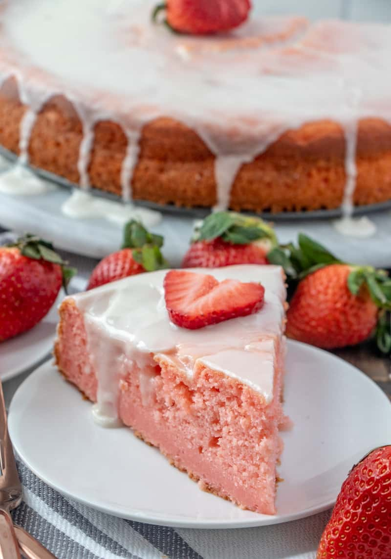 Slice of ricotta cake on white plate with sliced strawberry one top