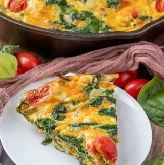 Vegetable frittata on white plate showing spinach and tomatoes