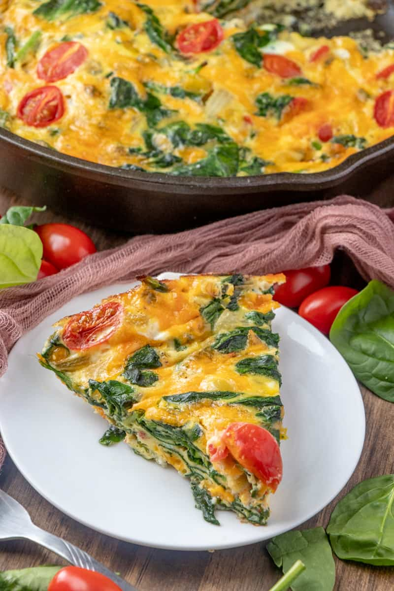 Vegetable Frittata sliced and plated surrounded by tomatoes and spinach leaves
