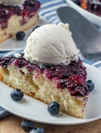 square photo of blueberry upside down cake on white plate garnished with fresh blueberries