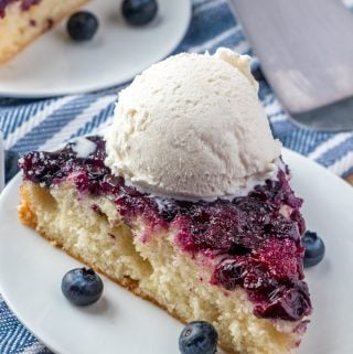 blueberry upside down cake on white plate topped with a scoop of ice cream