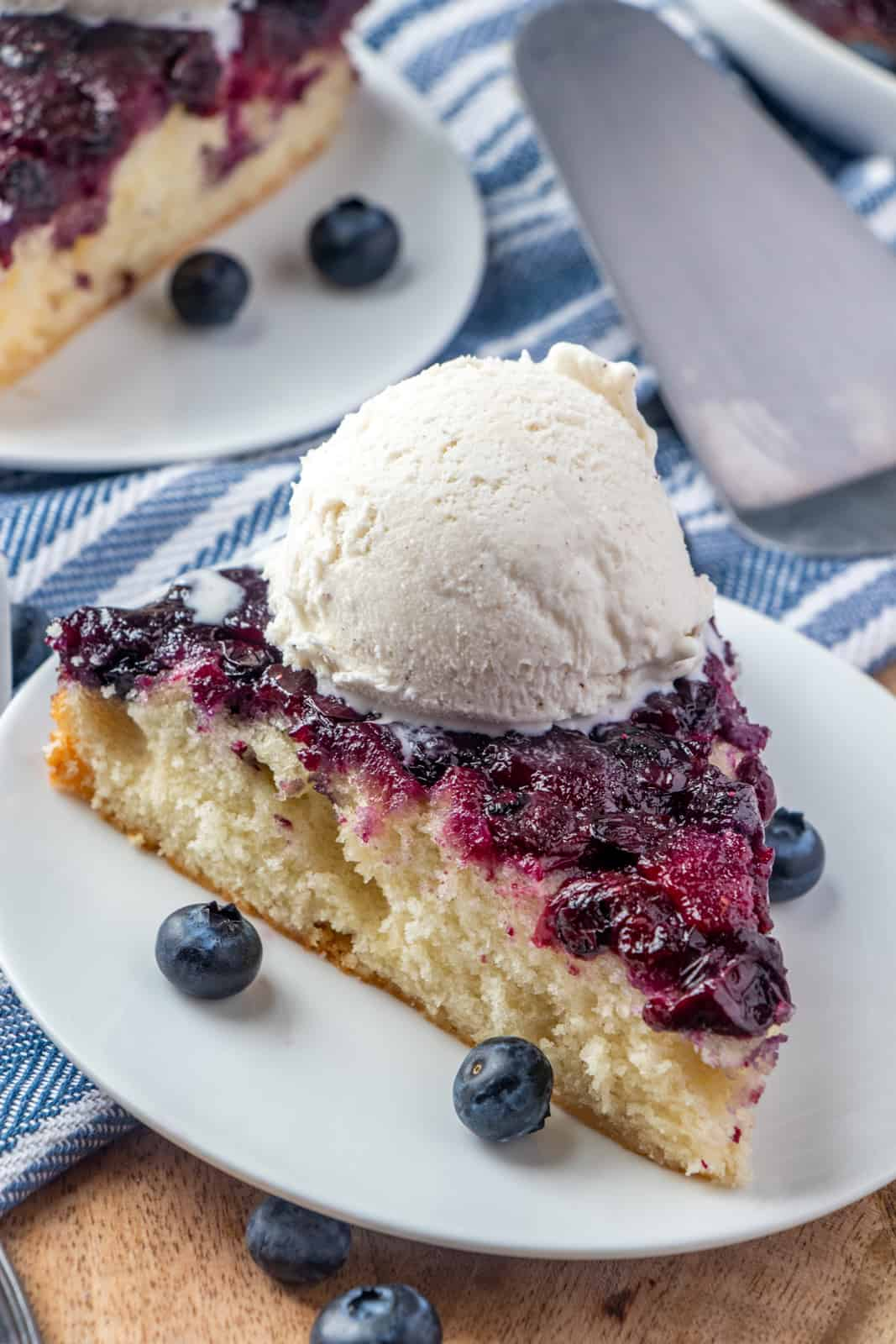 Close up of cake on plate with ice cream melting and blueberries on plate