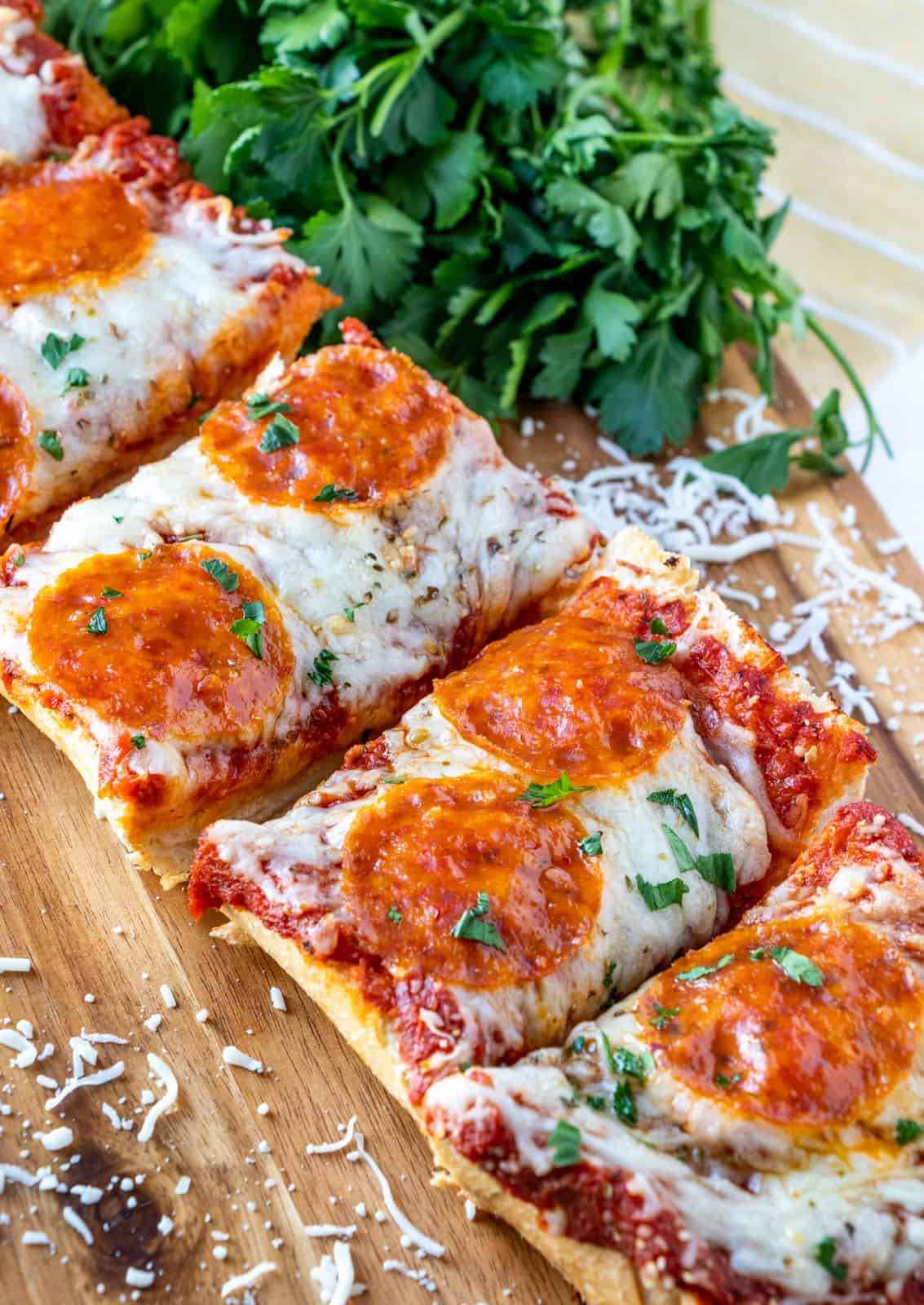 Sliced French Bread Pizza on cutting board with shredded cheese and parsley