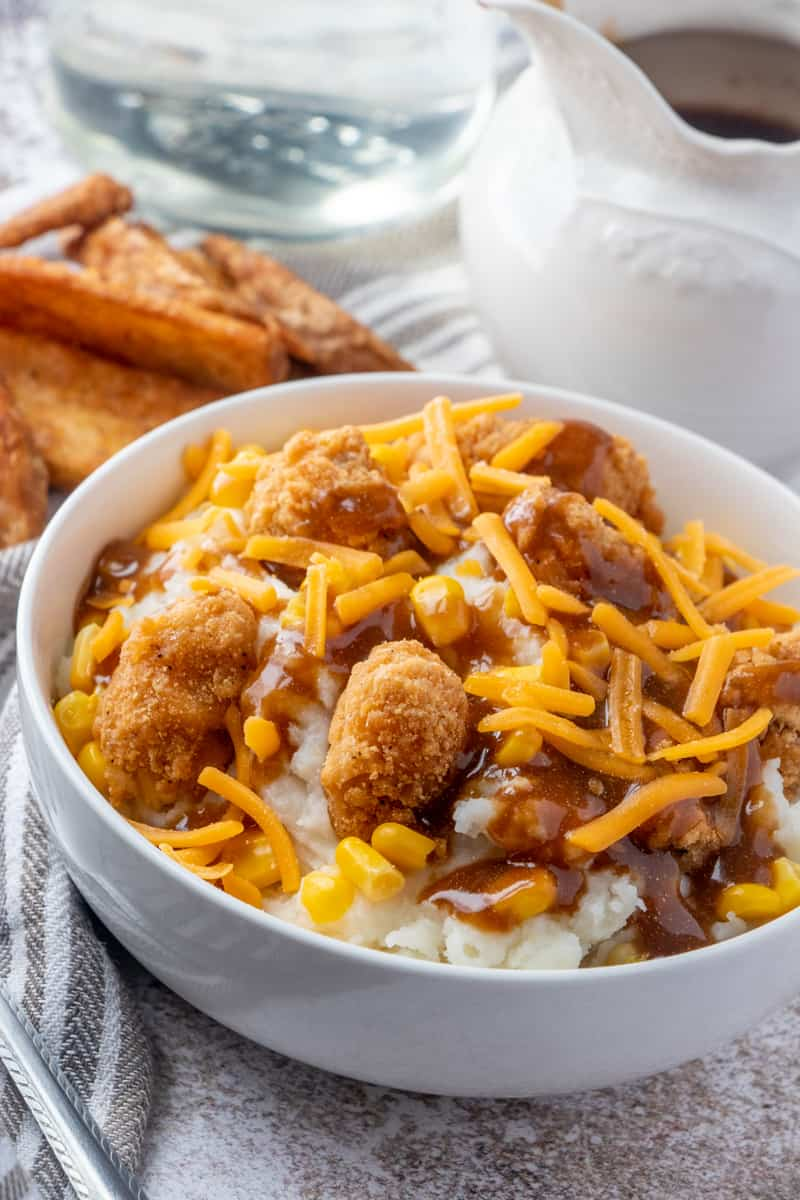 KFC Bowl with potato wedges in background and a gravy spout