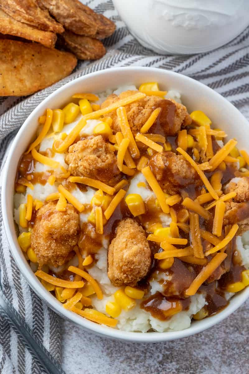 Overhead photo of bowl with potatoes, chicken, corn, gravy and cheese with potato wedges
