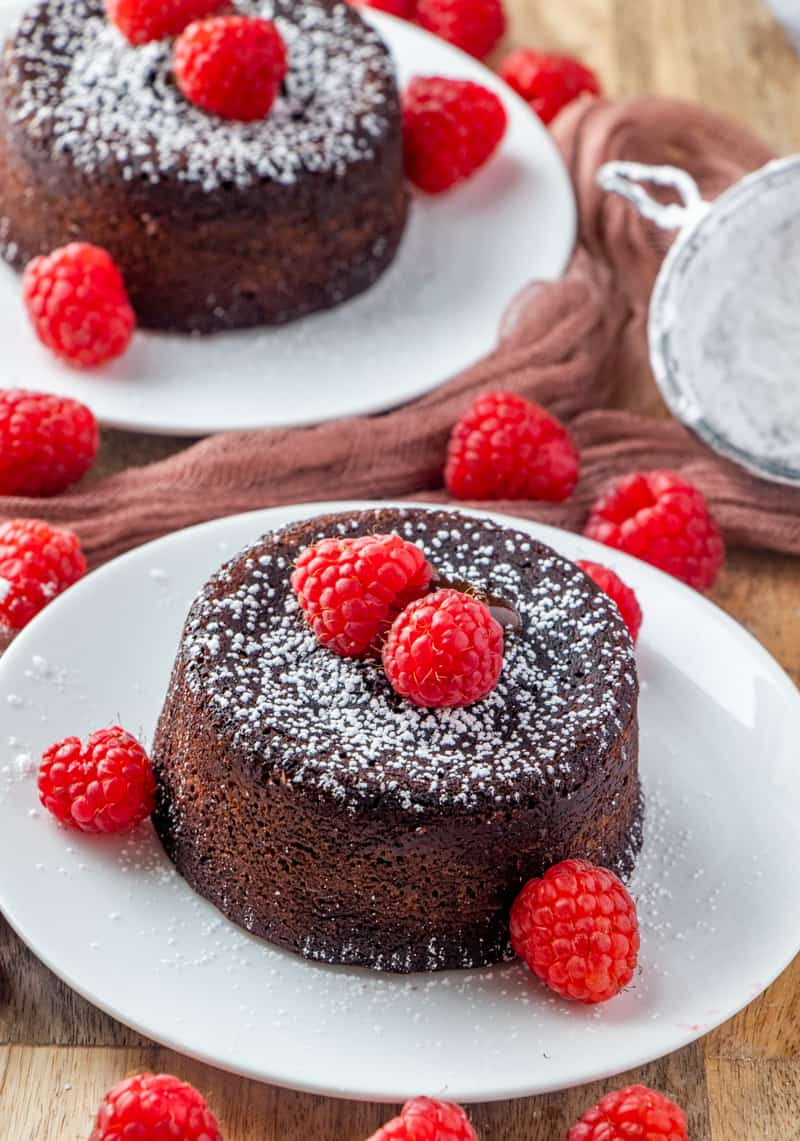 Chocolate Lava Cakes on plates topped with raspberries and powdered sugar
