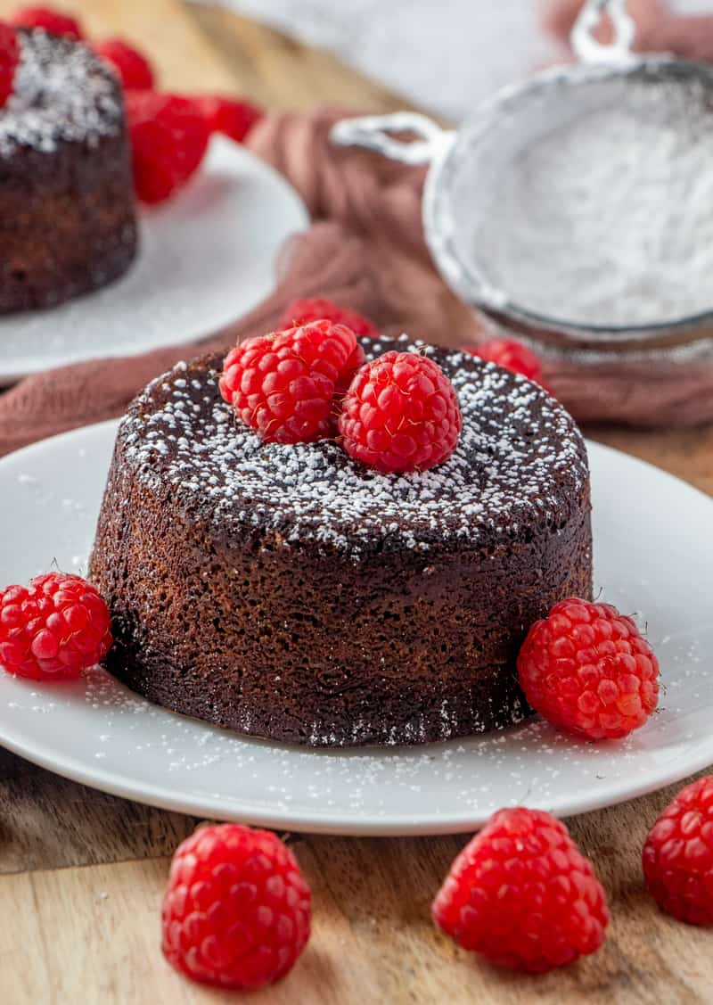 Plated cake on white round plate with sifted powdered sugar in back ground