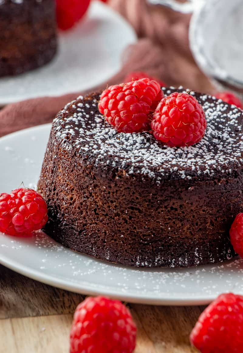Side view of lava cake on plate close up with raspberries