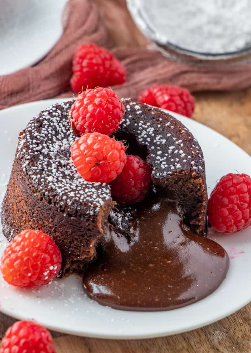 Chocolate pouring out center of baked lava cake topped with raspberries and powdered sugar