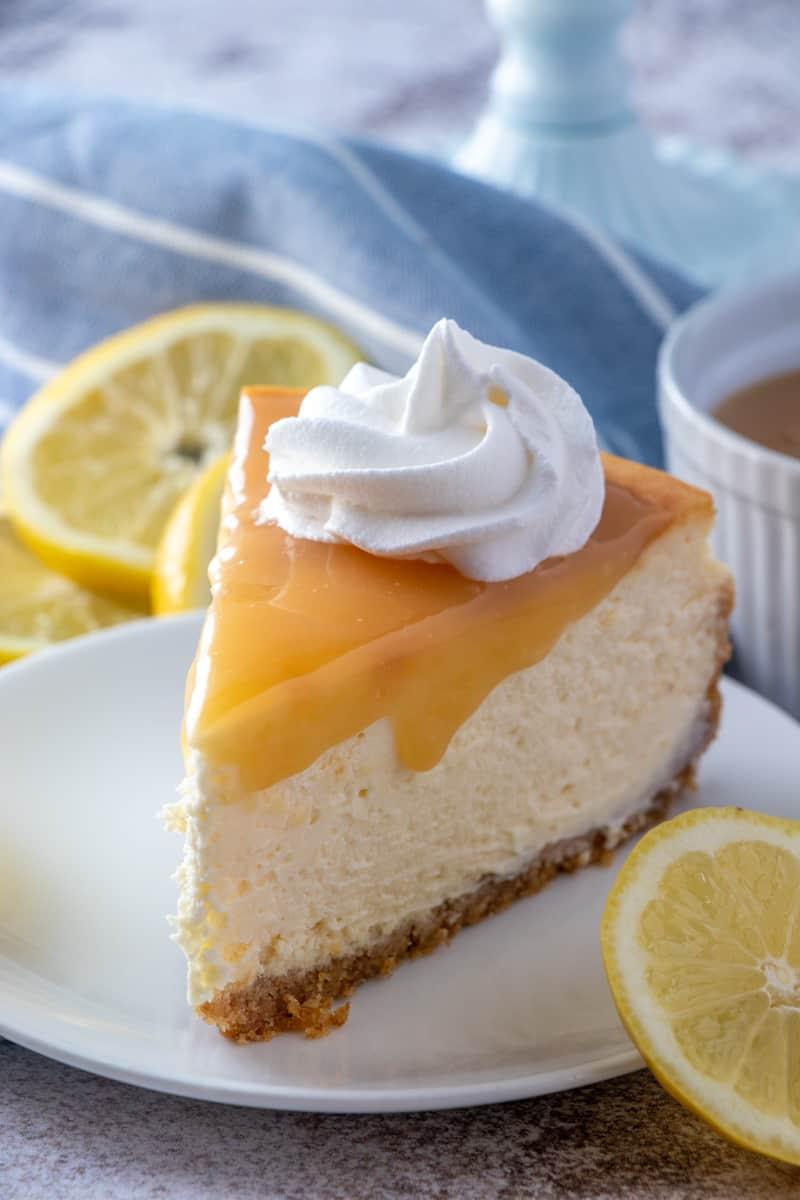Slice of cheesecake on white plate with lemon garnish