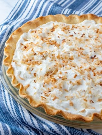finished coconut cream pie in pie plate topped with toasted coconut