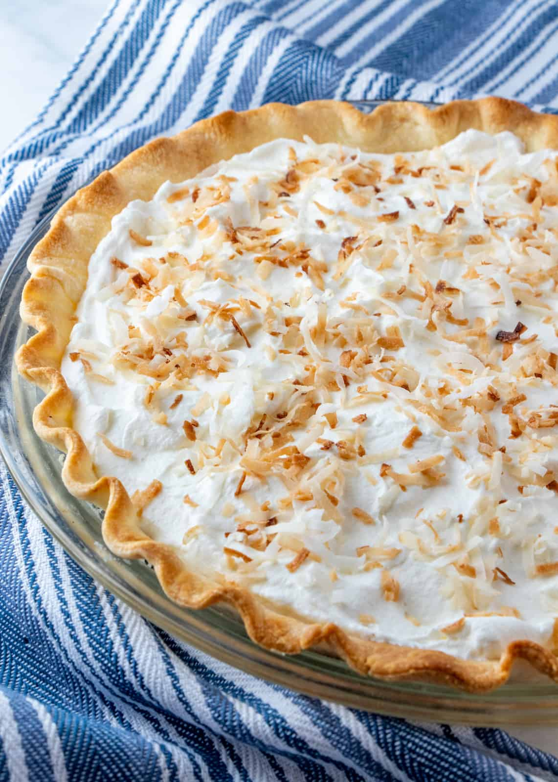 Finished pie uncut in pie pate topped with whipped cream and toasted coconut