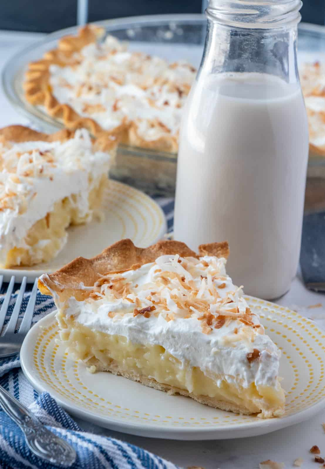 Two slices of pie on plates with cut pie in background with glass of milk