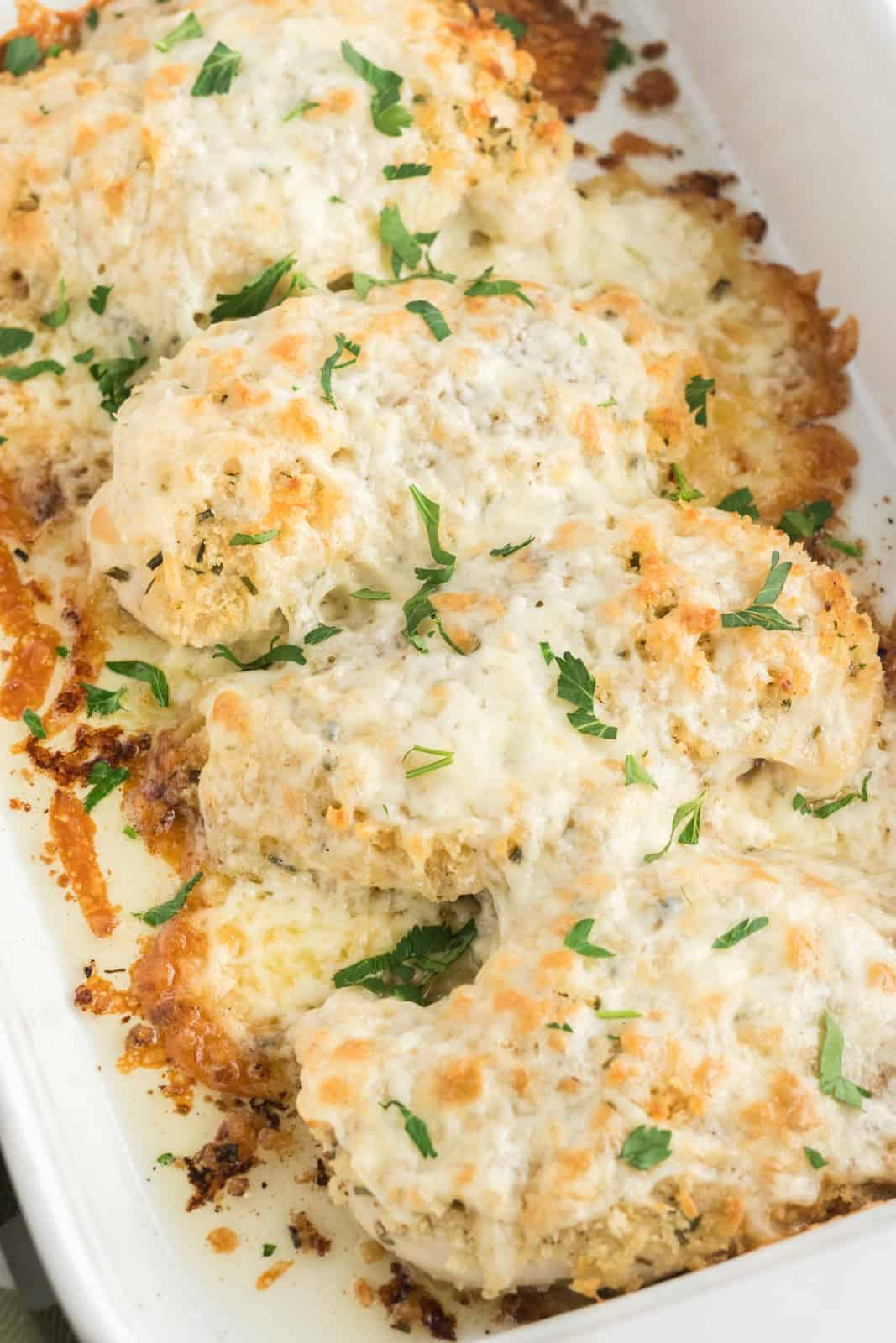 Finished Cheesy Chicken in baking dish topped with parsley